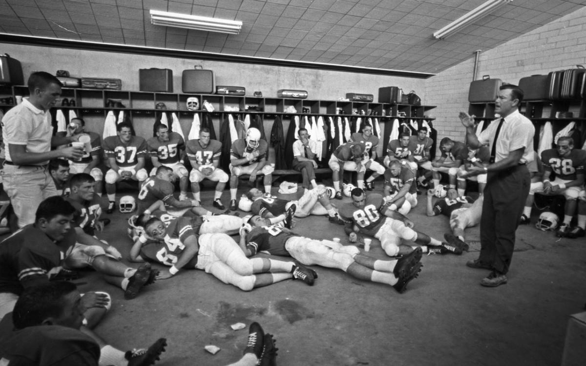 Texas coach Darrell Royal talking to team in locker room after game vs Oklahoma at Cotton Bowl Stadium.