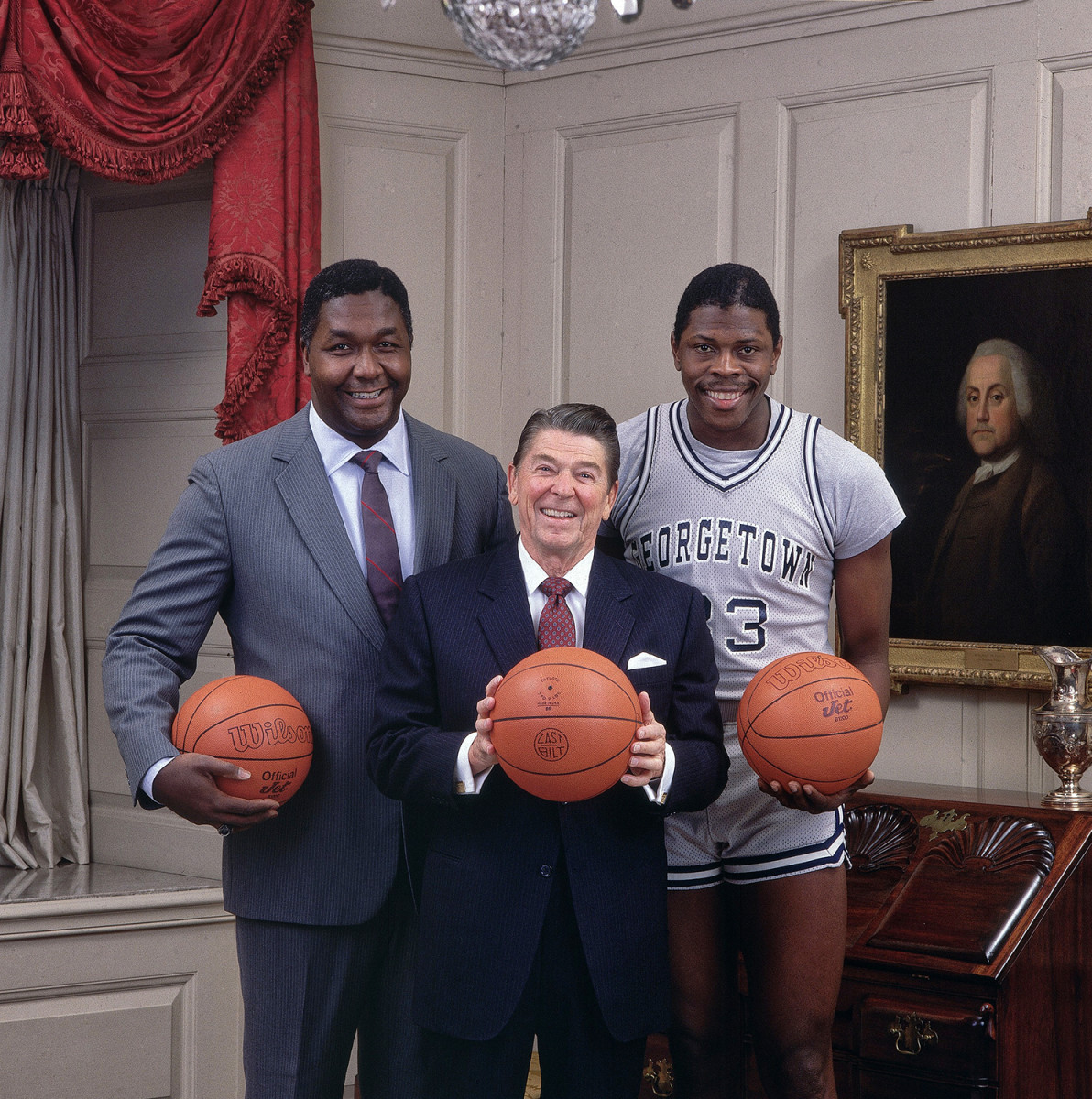Portrait of United States President Ronald Reagan with Georgetown coach John Thompson (L) and Patrick Ewing (33) during photo shoot at White House.