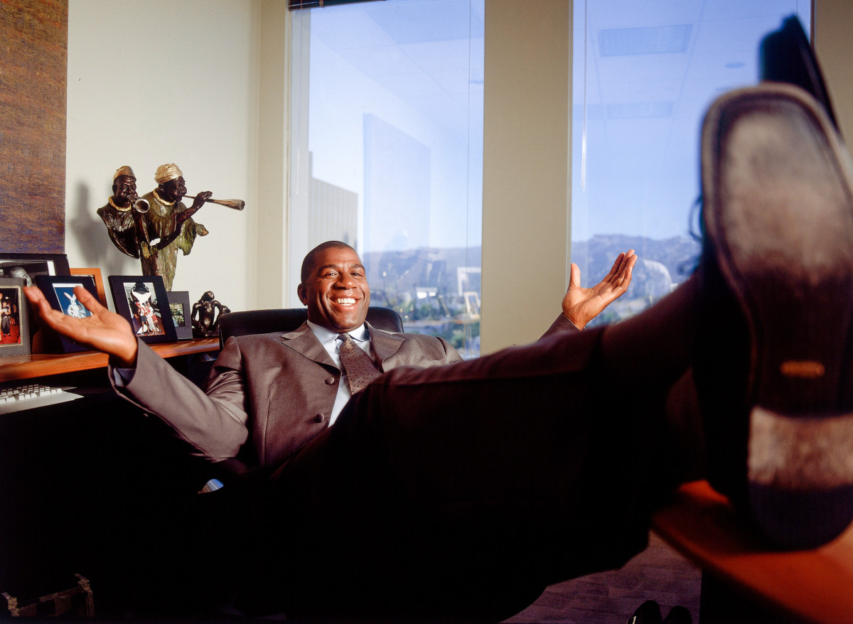 Former Laker Earvin (Magic) Johnson poses at his desk in his office in Beverly Hills, CA in July, 2001.