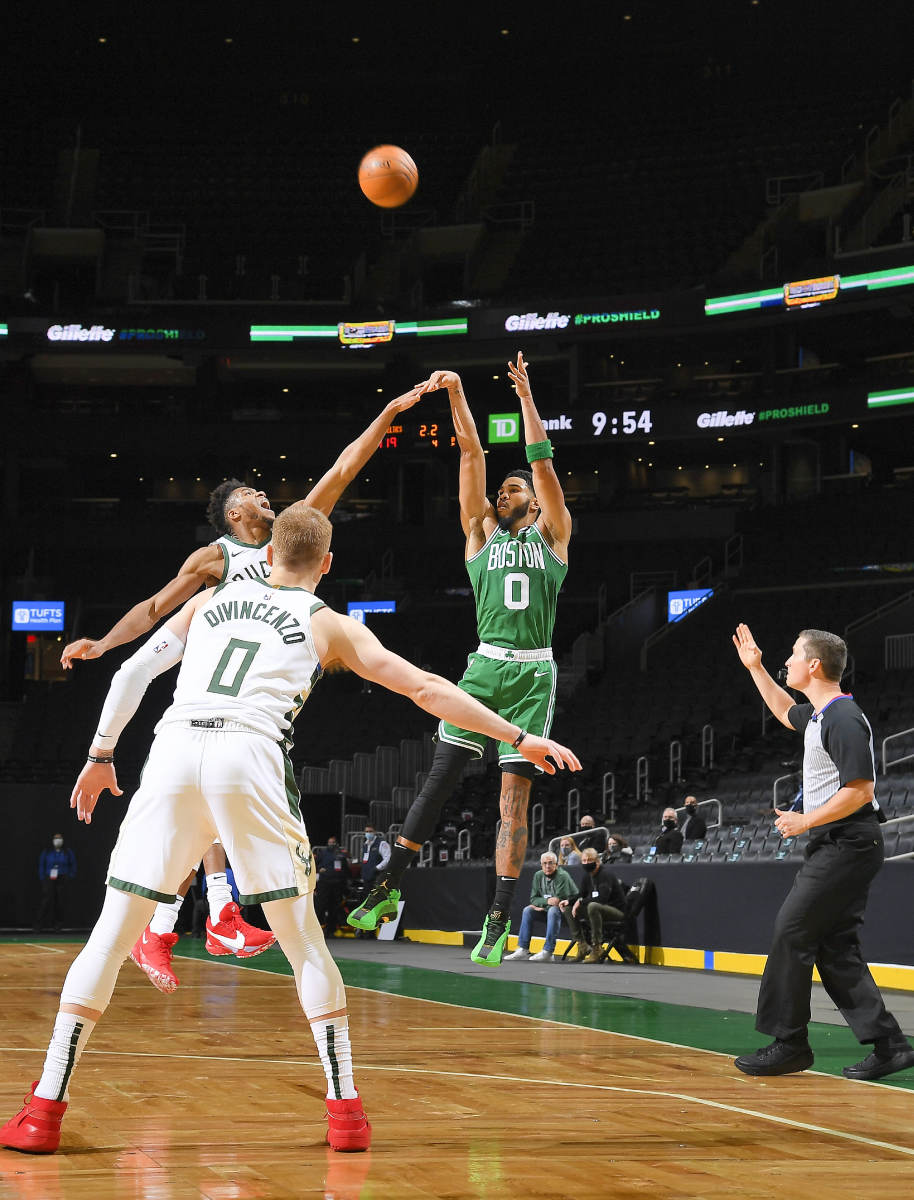 TRIPLE THREAT Tatum—who is averaging more than twice as many three-point attempts as he did two years ago when he relied on midrange Js—nailed a three to beat the Bucks in the season opener.